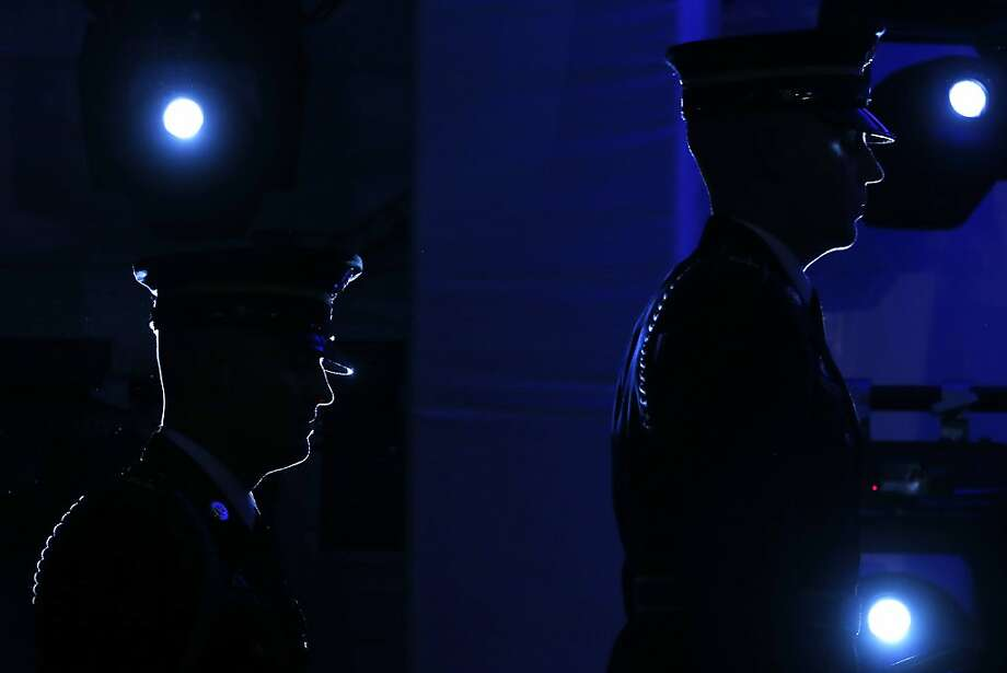 Military honor guard are illuminated by stage lights as they return to retrieve flags on stage at the end of the ceremony for the 20th anniversary of the United States Holocaust Memorial Museum in Washington, Monday, April 29, 2013. (AP Photo/Charles Dharapak) Photo: Charles Dharapak, Associated Press