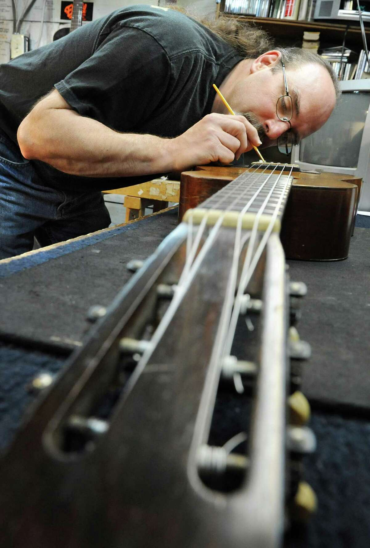 Steven Kovacik finishes shellac touch up on a 1919 Martin guitar as he works in his basement shop on Thursday, March 28, 2013 in Scotia, N.Y. (Lori Van Buren / Times Union)