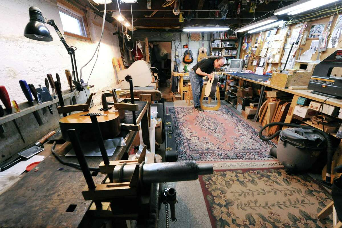 Steven Kovacik removes the custom built D-28 style guitar from the outside form as he works in his basement shop on Thursday, March 28, 2013 in Scotia, N.Y. (Lori Van Buren / Times Union)