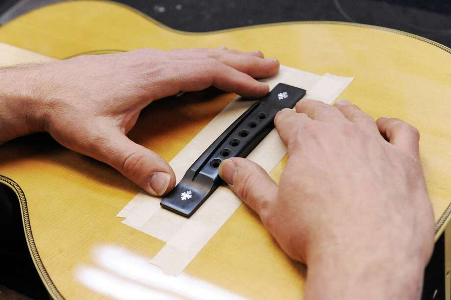 Steven Kovacik prepares to glue a bridge on a custom guitar as he works in his basement shop on Thursday, March 28, 2013 in Scotia, N.Y.  (Lori Van Buren / Times Union) Photo: Lori Van Buren