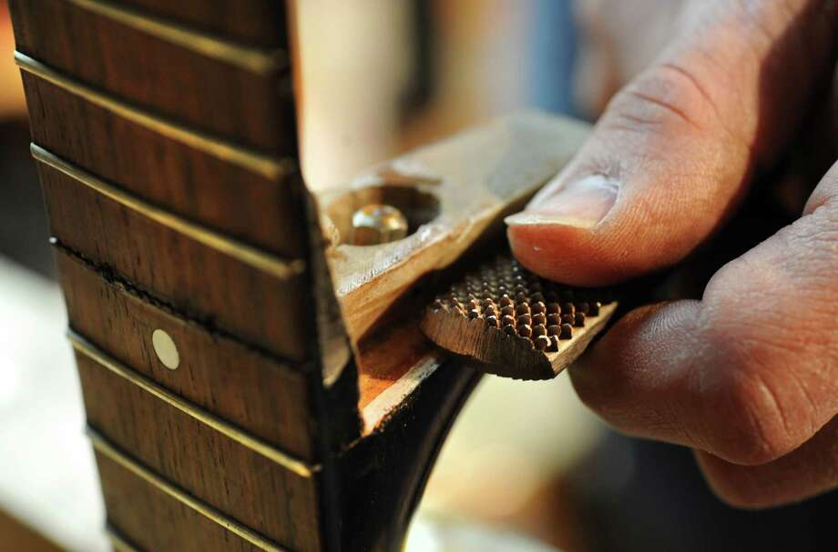 Steven Kovacik trims the heel on a 1930's Gibson guitar that is in the shop for a neck reset as he works in his basement shop on Thursday, March 28, 2013 in Scotia, N.Y.  (Lori Van Buren / Times Union) Photo: Lori Van Buren
