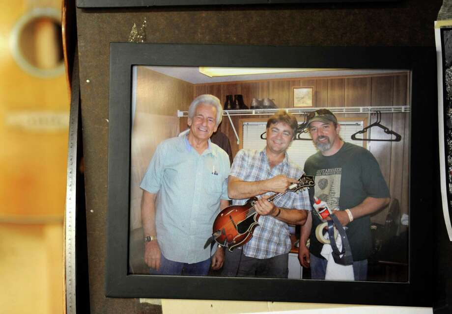 From left, a photograph of bluegrass legends Del McCoury and Ronnie McCoury with Steven Kovacik hangs on the wall in the basement shop Steven's wall on Thursday, March 28, 2013 in Scotia, N.Y. The mandolin was damaged backstage at Greyfox Bluegrass Festival and was repaired by Kovacik moments before the McCourys took the stage. (Lori Van Buren / Times Union) Photo: Lori Van Buren