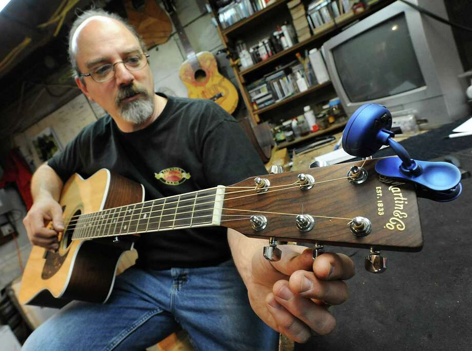 Steven Kovacik uses an electronic tuner to tune a guitar as he works in his basement shop on Thursday, March 28, 2013 in Scotia, N.Y.  (Lori Van Buren / Times Union) Photo: Lori Van Buren