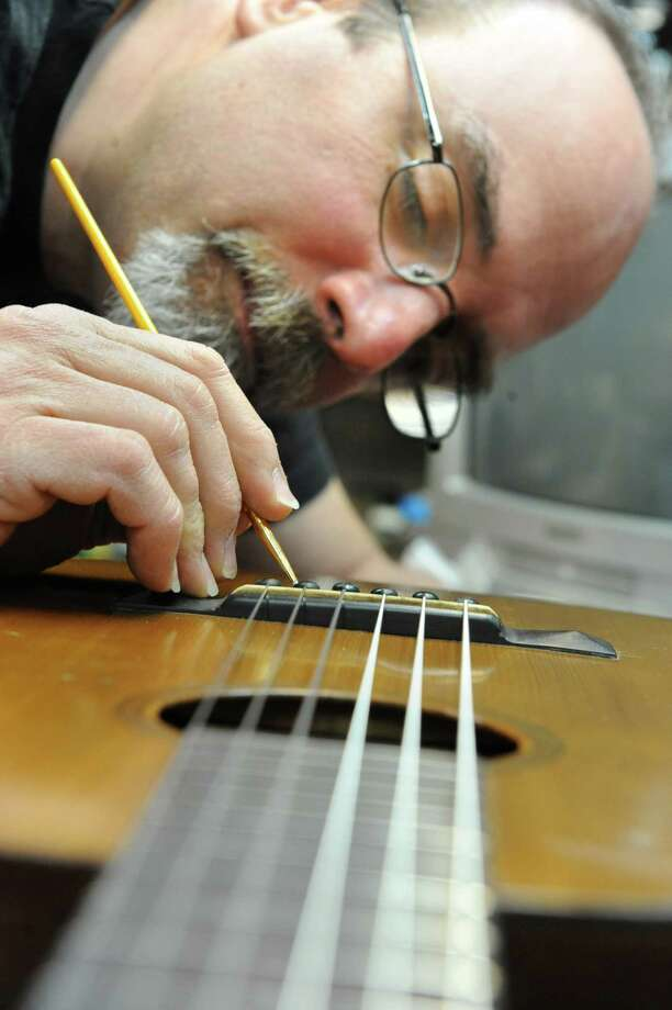 Steven Kovacik finishes shellac touch up on a 1919 Martin guitar as he works in his basement shop on Thursday, March 28, 2013 in Scotia, N.Y.  (Lori Van Buren / Times Union) Photo: Lori Van Buren