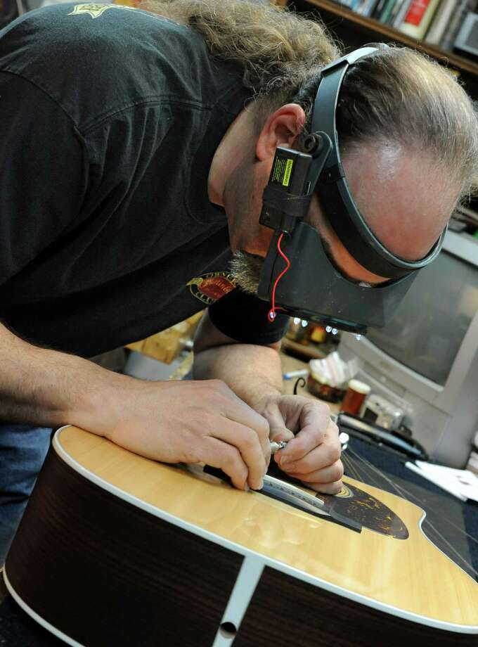 Steven Kovacik uses an Opti-visor while re-profiling a guitar saddle as he works on a customer's guitar in his basement shop on Thursday, March 28, 2013 in Scotia, N.Y.  (Lori Van Buren / Times Union) Photo: Lori Van Buren