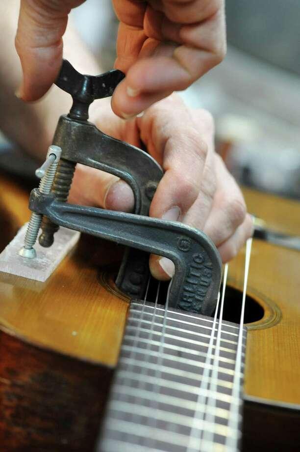 Steven Kovacik clamps a top crack repair on a 1919 Martin guitar as he works in his basement shop on Thursday, March 28, 2013 in Scotia, N.Y.  (Lori Van Buren / Times Union) Photo: Lori Van Buren