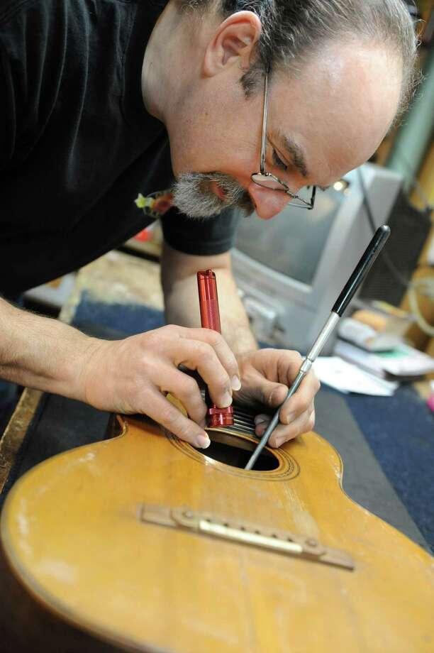 Steven Kovacik examines the bracings and bridge plate on a 19 century Martin guitar as he works in his shop on Thursday, March 28, 2013 in Scotia, N.Y.  (Lori Van Buren / Times Union) Photo: Lori Van Buren