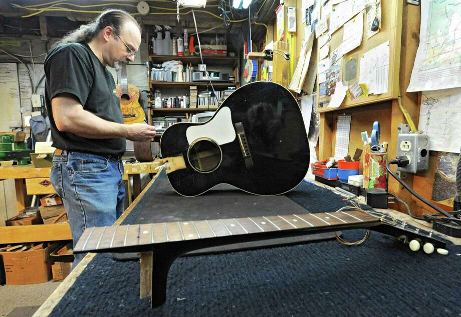 Steven Kovacik works on a 1930's Gibson guitar that is in the shop for a neck reset as he works in his basement shop on Thursday, March 28, 2013 in Scotia, N.Y.  (Lori Van Buren / Times Union) Photo: Lori Van Buren