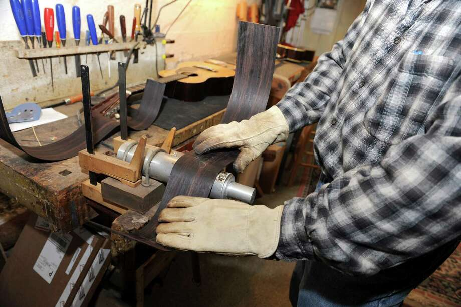 Steven Kovacik uses a bending iron to make the curved part of the indian rosewood to be used for his 000 size guitar in his basement shop on Thursday, March 28, 2013 in Scotia, N.Y.  (Lori Van Buren / Times Union) Photo: Lori Van Buren