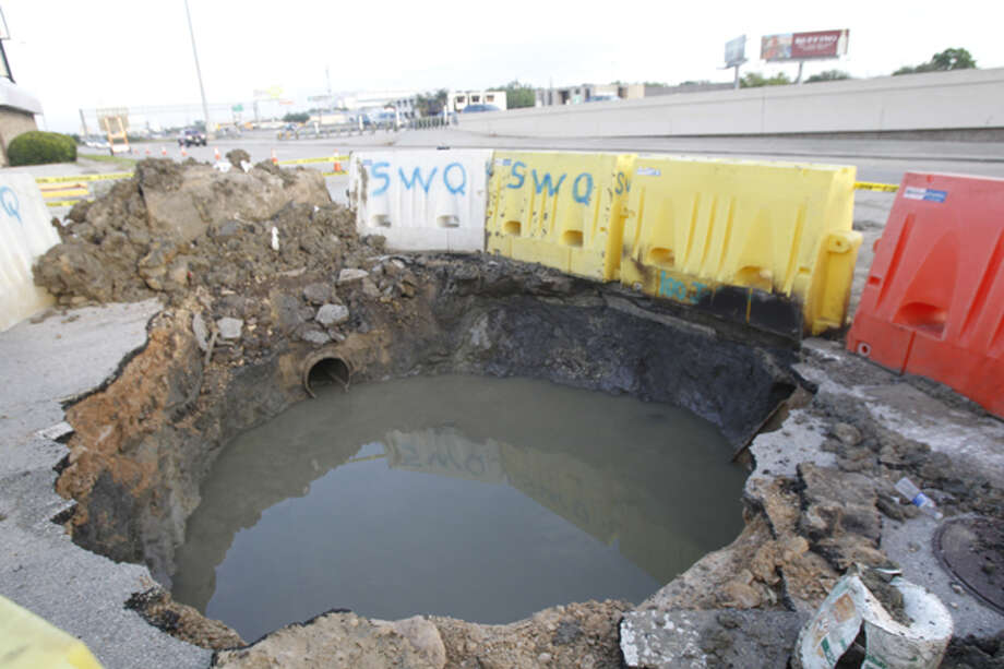Work crews are trying to repair this large sinkhole along the 610 Loop in southeast Houston. It opened up about 3:30 p.m. Monday near Almeda and grew overnight to about 12 feet wide, officials say. Photo: Cody Duty / Houston Chronicle