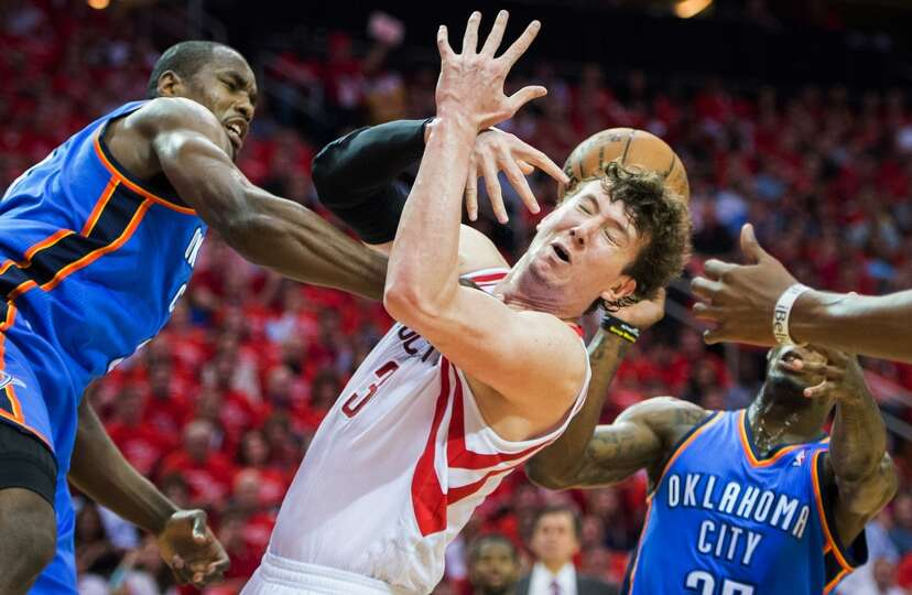 Serge Ibaka of the thunder pokes the ball away from Rockets center Omer Asik.