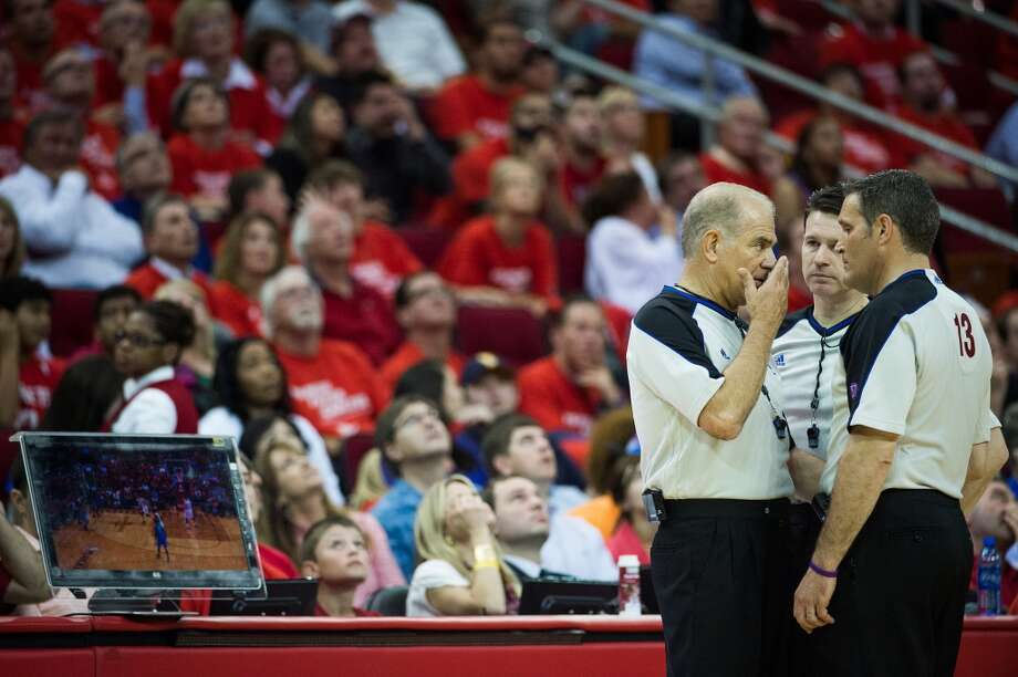 Referees Bennett Salvatore, Bob Delaney and Monty McCutchen huddle before a video replay that overturned a 3-pointer by Derek Fisher in the closing minutes. Photo: Smiley N. Pool, Houston Chronicle