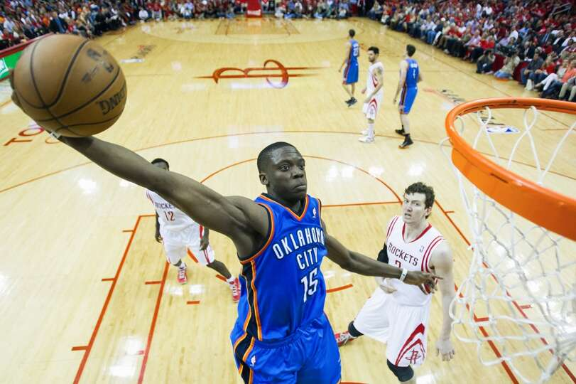 Thunder guard Reggie Jackson dunks past Rockets guard Patrick Beverley and center Omer Asik during t