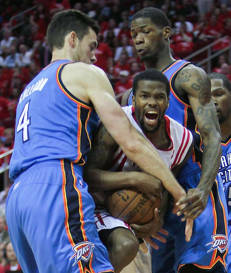 Rockets point guard Aaron Brooks is double-teamed by Thunder forward Nick Collison and the guard DeAndre Liggins. Photo: James Nielsen, Houston Chronicle