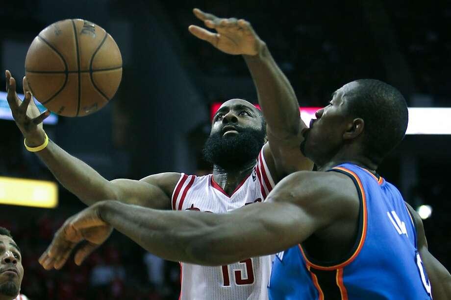 Rockets guard James Harden drives to the basket past the Thunder power forward Serge Ibaka. Photo: James Nielsen, Houston Chronicle
