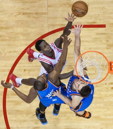 Patrick Beverley shoots over Thunder forwards Kevin Durant and Nick Collison.