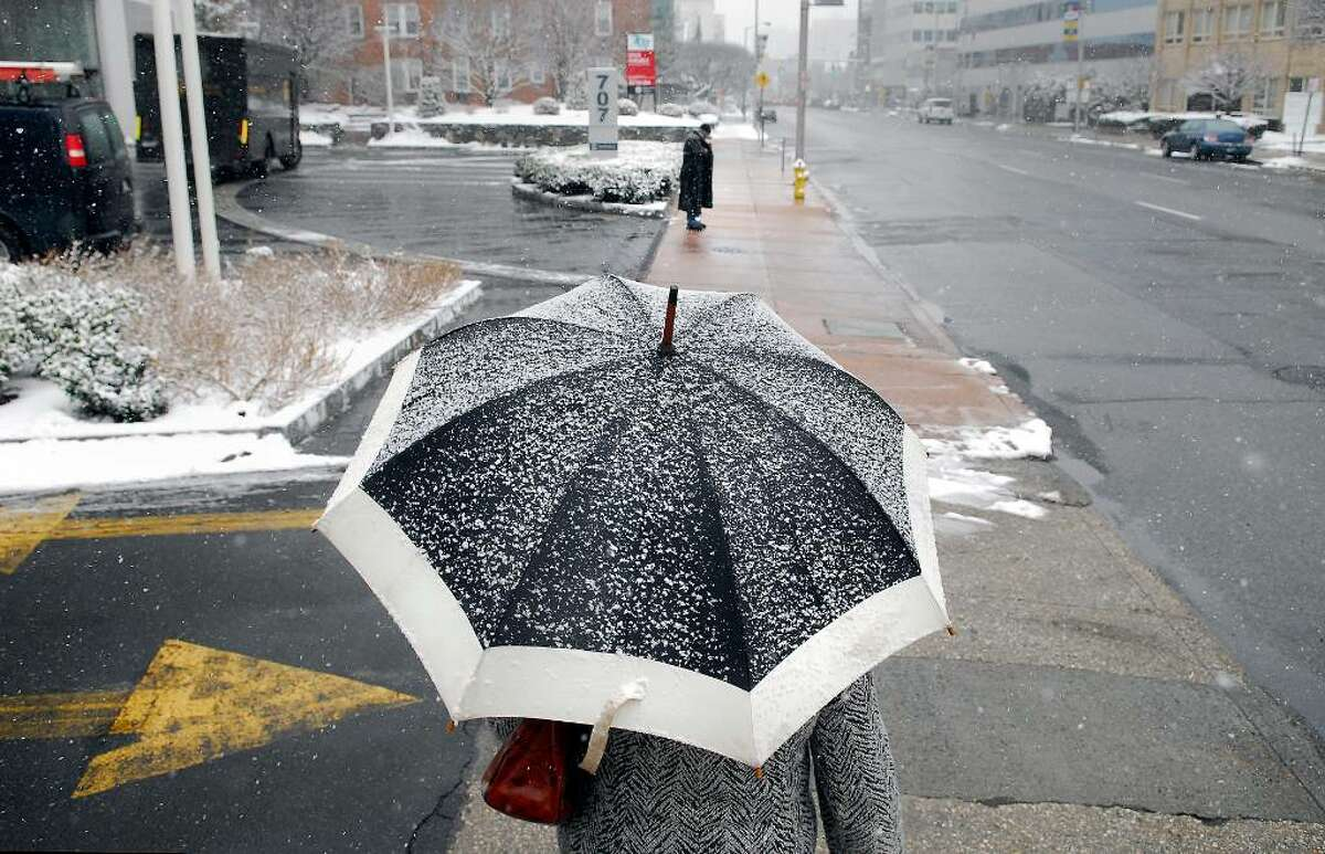 Helen Nawrocka of Stamford uses an umbrella to shield herself from the light snow Friday morning Jan. 8th, 2010, as she walks south on a deserted Summer Street.