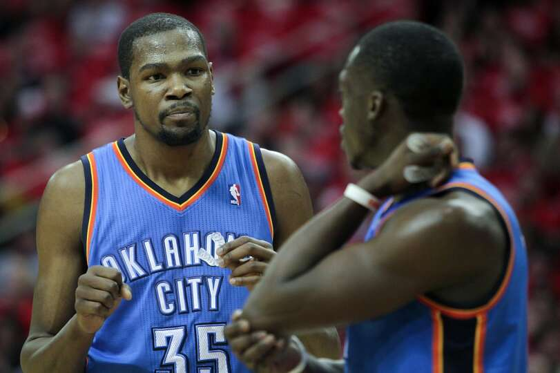 Thunder players Kevin Durant and Reggie Jackson share a word on the court.