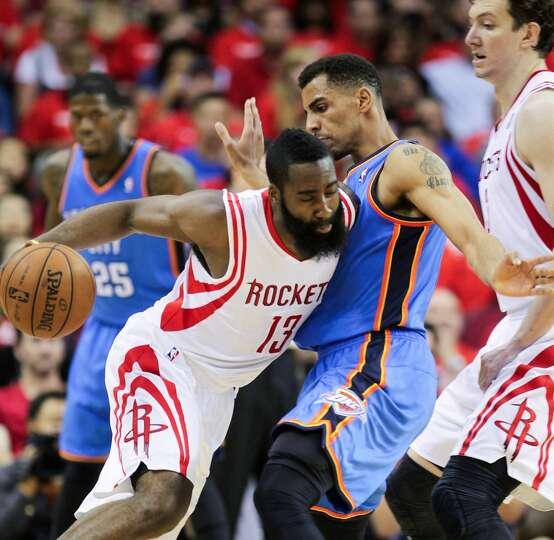 Thabo Sefolosha of the Thunder defends Rockets shooting guard James Harden.