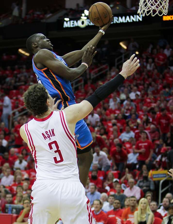 Thunder power forward Serge Ibaka shoots over the Rockets center Omer Asik. Photo: James Nielsen, Houston Chronicle