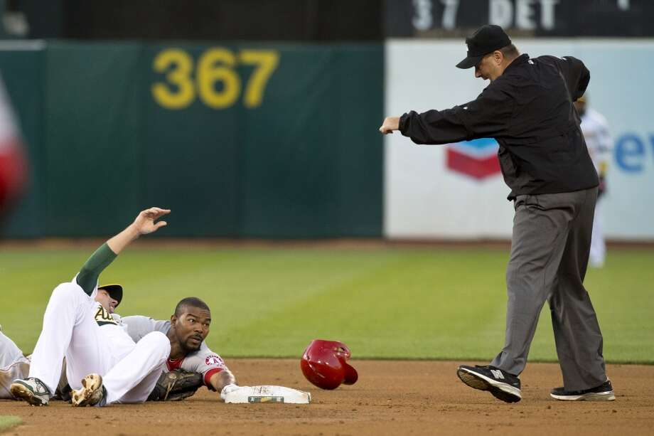 Howie Kendrick (47) of the Los Angeles Angels of Anaheim is called out by umpire Gary Cederstrom #38 after getting tagged out at second base by Jed Lowrie #8 of the Oakland Athletics during the second inning at O.co Coliseum on April 29, 2013 in Oakland, California.