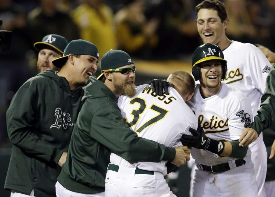 Oakland Athletics' Brandon Moss (37) is mobbed by teammates after his game-winning two-run home run against the Los Angeles Angels during a baseball game on Tuesday, April 30, 2013 in Oakland. Calif. Oakland won 10-8 in 19 innings.