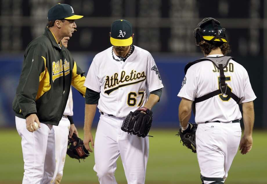 Oakland Athletics starting pitcher Dan Straily (67) is pulled from the game by manager Bob Melvin, left, during the fifth inning of a baseball game against the Los Angeles Angels on Monday, April 29, 2013 in Oakland. Calif.