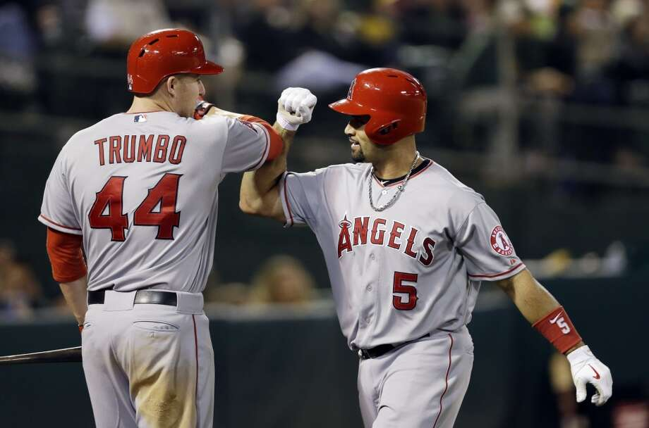 Los Angeles Angels' Albert Pujols (5) celebrates his solo home run with teammate Mark Trumbo (44) against the Oakland Athletics during the seventh inning of a baseball game on Monday, April 29, 2013 in Oakland. Calif.