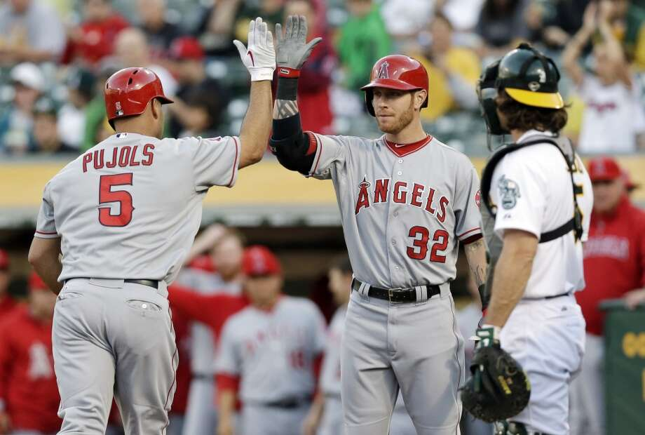 Los Angeles Angels' Albert Pujols (5) celebrates his a solo home run against the Oakland Athletics with teammate Josh Hamilton (32) during the first inning of a baseball game on Monday, April 29, 2013 in Oakland. Calif.