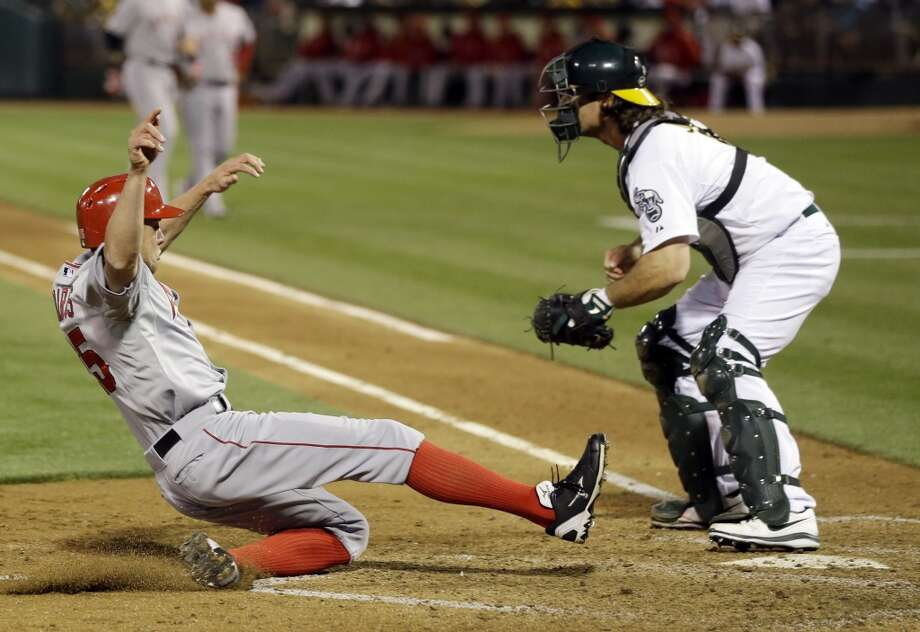 Los Angeles Angels' Peter Bourjos, left, scores past Oakland Athletics catcher John Jaso on a sacrifice fly ball from Los Angeles Angels' Josh Hamilton during the fifth inning of a baseball game on Monday, April 29, 2013 in Oakland. Calif.