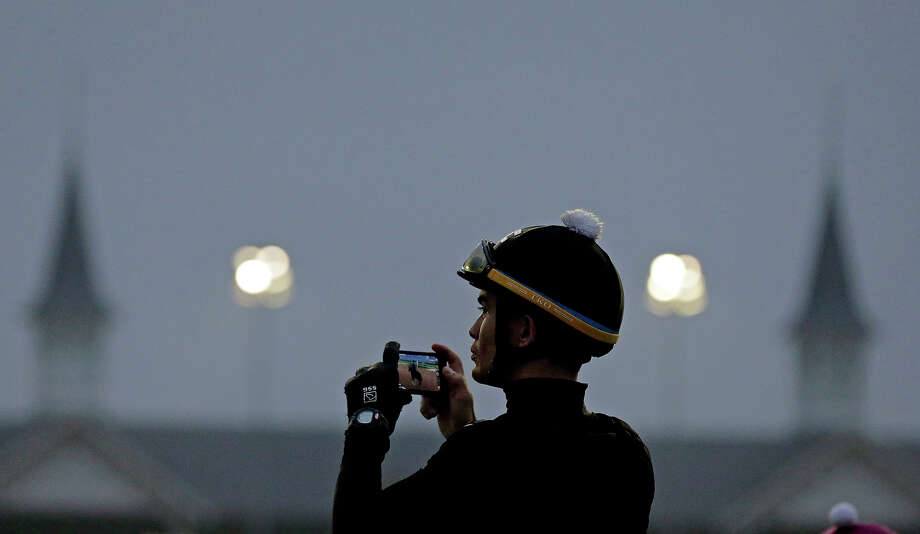 Abel Flores takes some pictures as the sun comes up at Churchill Downs Monday, April 29, 2013, in Louisville, Ky. Photo: Charlie Riedel, ASSOCIATED PRESS / AP2013
