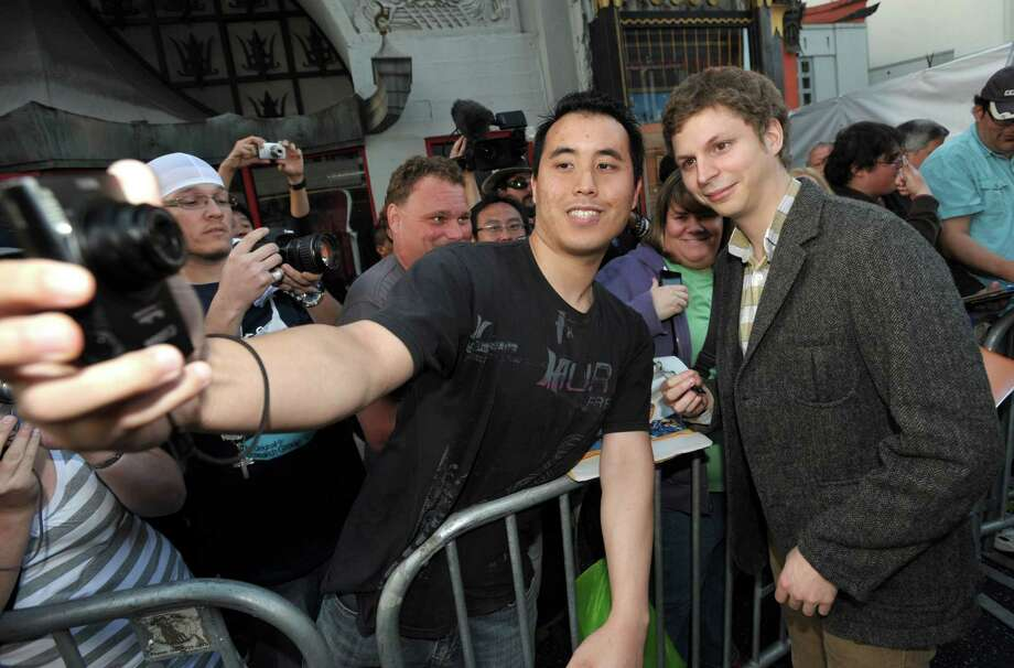 "Michael Cera, right, greets fans at the season four premiere of ""Arrested Development"" at the TCL Chinese Theatre on Monday, April 29, 2013 in Los Angeles. Photo: John Shearer, John Shearer/Invision/AP / Invision"