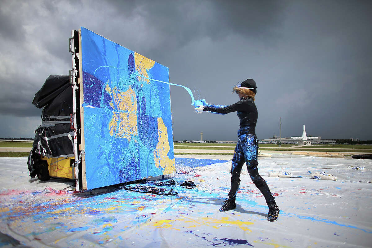 Artist Princess Tarinan von Anhalt throws paint into the flow of air coming from the engine of Flexjet's Learjet 40 XR engine to create a painting on a canvas at Signature Flight Support on April 30, 2013 in West Palm Beach, Florida. The artist associated with the Jet Art Group used the help of Flexjet and their plane to spray paint on a canvas to create distinctive paintings to celebrate the 50th anniversary of Learjet.