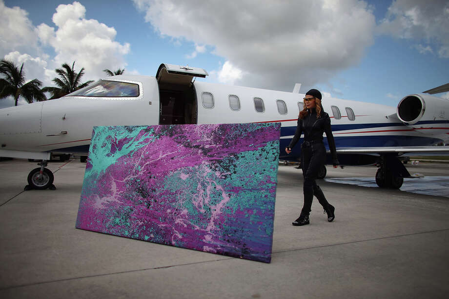Artist Princess Tarinan von Anhalt  walks near a piece of her art that was created using the air flow coming from the engine of Flexjet's Learjet 40 XR engine at Signature Flight Support on April 30, 2013 in West Palm Beach, Florida.  The artist associated with the Jet Art Group used the help of Flexjet and their plane to spray paint on a canvas to create distinctive paintings to celebrate the 50th anniversary of Learjet. Photo: Joe Raedle, Getty Images / 2013 Getty Images