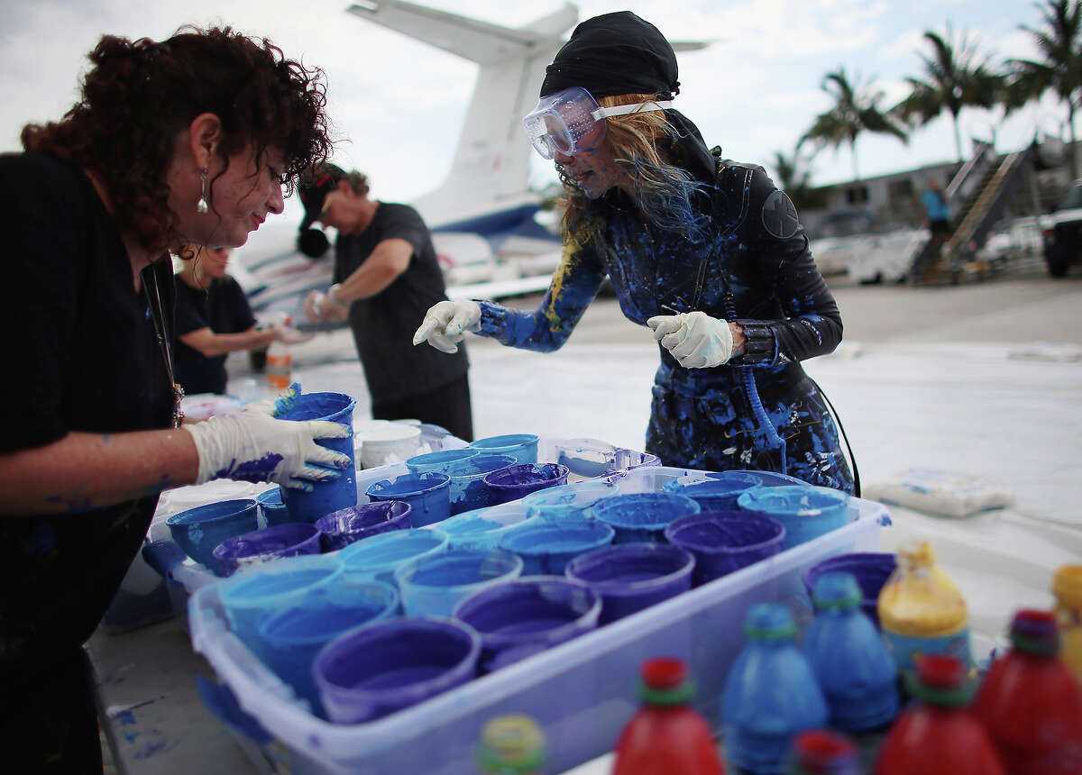 Artist Princess Tarinan von Anhalt (R) picks her paint color as she works on a piece of art using the air flow coming from the engine of Flexjet's Learjet 40 XR engine at Signature Flight Support on April 30, 2013 in West Palm Beach, Florida. The artist associated with the Jet Art Group used the help of Flexjet and their plane to spray paint on a canvas to create distinctive paintings to celebrate the 50th anniversary of Learjet.