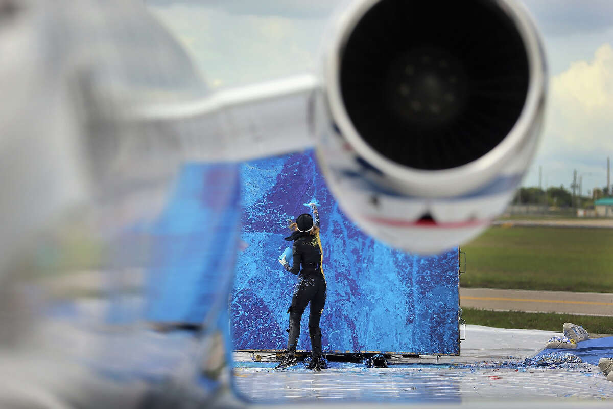 Artist Princess Tarinan von Anhalt works on a piece of art using the air flow coming from the engine of Flexjet's Learjet 40 XR engine at Signature Flight Support on April 30, 2013 in West Palm Beach, Florida. The artist associated with the Jet Art Group used the help of Flexjet and their plane to spray paint on a canvas to create distinctive paintings to celebrate the 50th anniversary of Learjet.