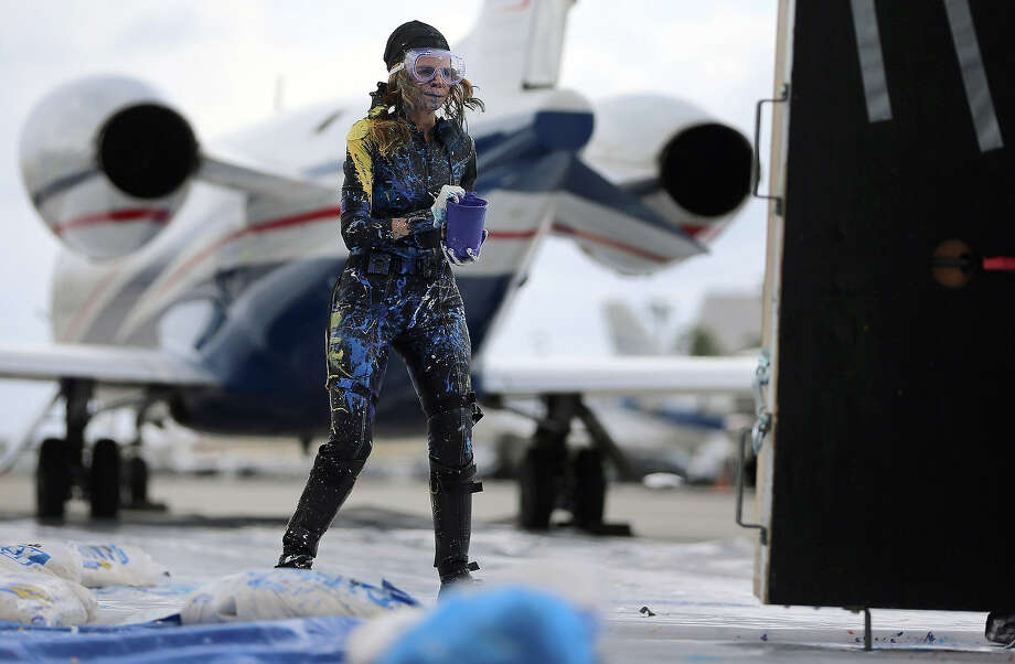 Artist Princess Tarinan von Anhalt works on a piece of art using the air flow coming from the engine of Flexjet?s Learjet 40 XR engine at Signature Flight Support on April 30, 2013 in West Palm Beach, Florida.  The artist associated with the Jet Art Group used the help of Flexjet and their plane to spray paint on a canvas to create distinctive paintings to celebrate the 50th anniversary of Learjet. Photo: Joe Raedle, Getty Images / 2013 Getty Images