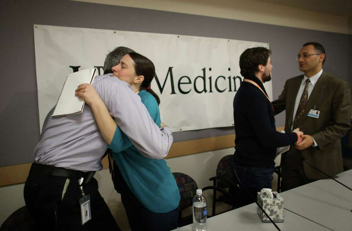 Marilyn Schulte hugs Dr. Francois Aspesberro, attending physician in Children's intensive care unit, as Dan Schulte shakes hands with Dr. Saman Arbabi, acute care section head at Harborview Injury Prevention and Research Center after a press conference.
