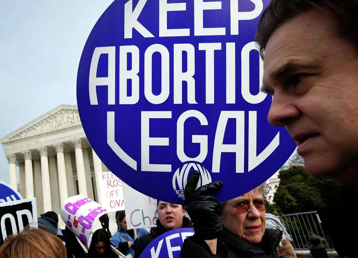 """2010: A pro-choice activist holds up a sign during the annual """"March for Life"""" event in front of U.S. Supreme Court January 22, 2010 in Washington, DC."""