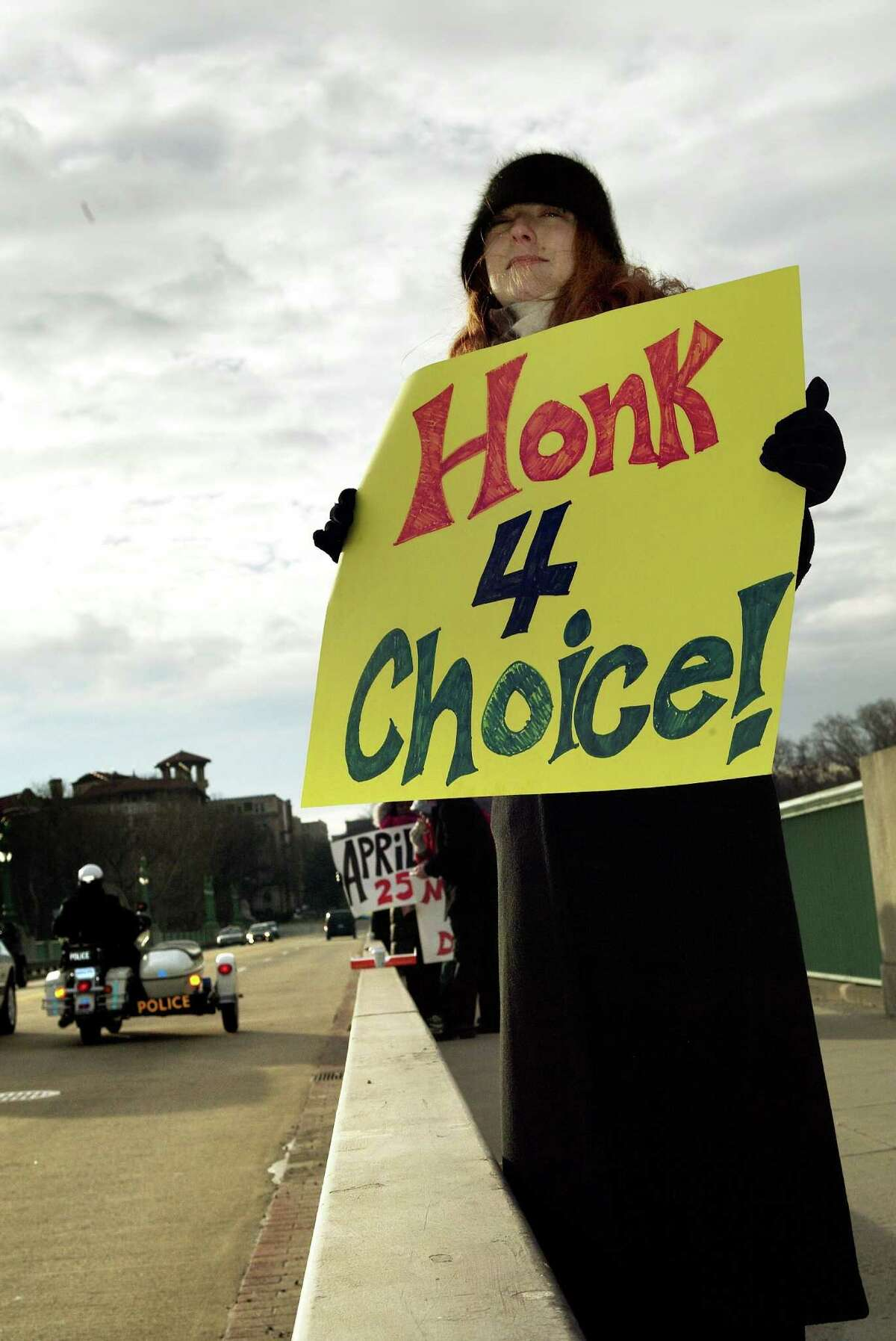 2004: Marisa Bassett rallies passing cars during a planned Parenthood rally on the Taft Bridge crossing Connecticut Avenue over Rock Creek Park January 22, 2004 in Washington, DC.