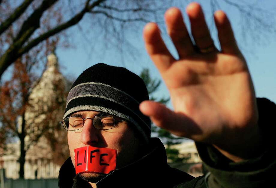 2005: Pro-life activist Jason Hershey prays in front of the U.S. Supreme Court with the group Bound for Life Nov. 30, 2005 in Washington, DC. The highest court in the U.S. is hearing the first case on abortion rights since Chief Justice John Roberts was sworn in. Photo: Win McNamee, Getty Images / 2005 Getty Images