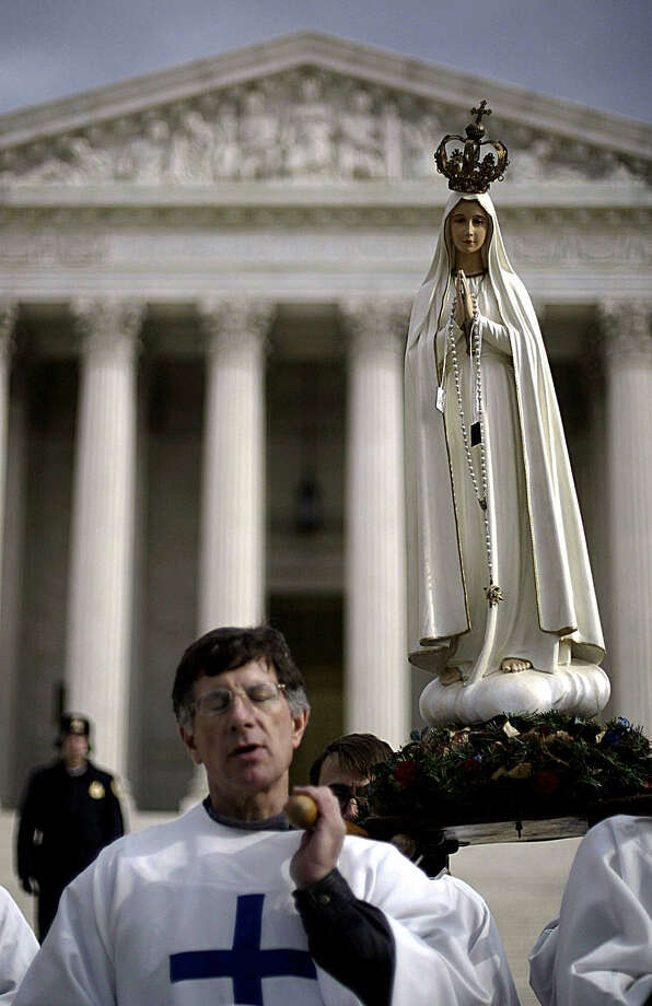 2004: Priests with The Fatima Center recite the rosary as they carry a statue of Our Lady of Fatima in front of the US Supreme Court during the March for Life demonstration in Washington, DC. Photo: TIM SLOAN, Getty Images / 2004 AFP