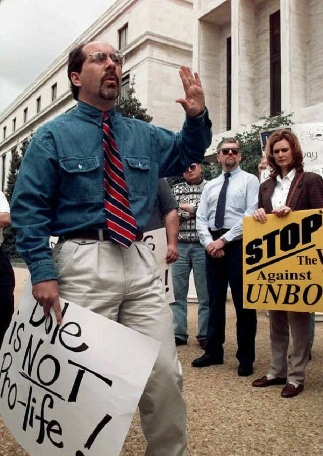 1996: Rev. Patrick J. Mahoney (L) leads members of the Christian Defense Coalition in a demonstration and prayer vigil outside of US Senator Bob Dole's office on Capitol Hill in Washington, DC. Photo: DAVID AKE, Getty Images / AFP