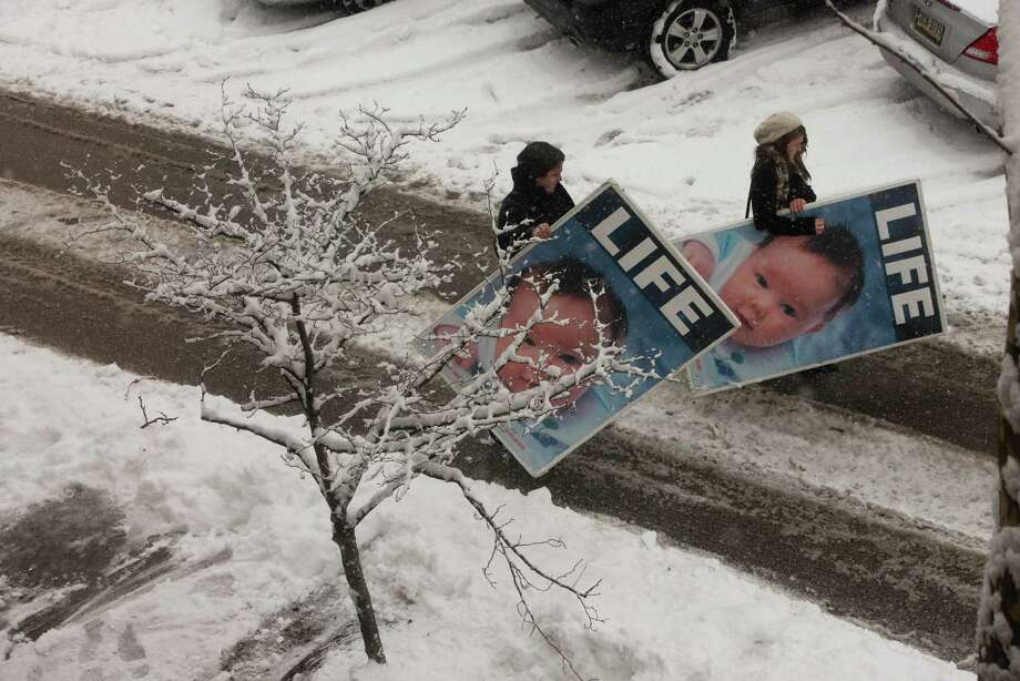 2012: In Pittsburgh, Penn., abortions are routinely done at the Allegheny Reproductive Health Center as the 40th anniversary of Roe vs. Wade is marked this month. Protestors, Nathanael Provan, 30, left, and Mary Brough, 19, carry signs to their car at the end of the day. Photo: Sarah L. Voisin, Getty Images / Sarah L. Voisin