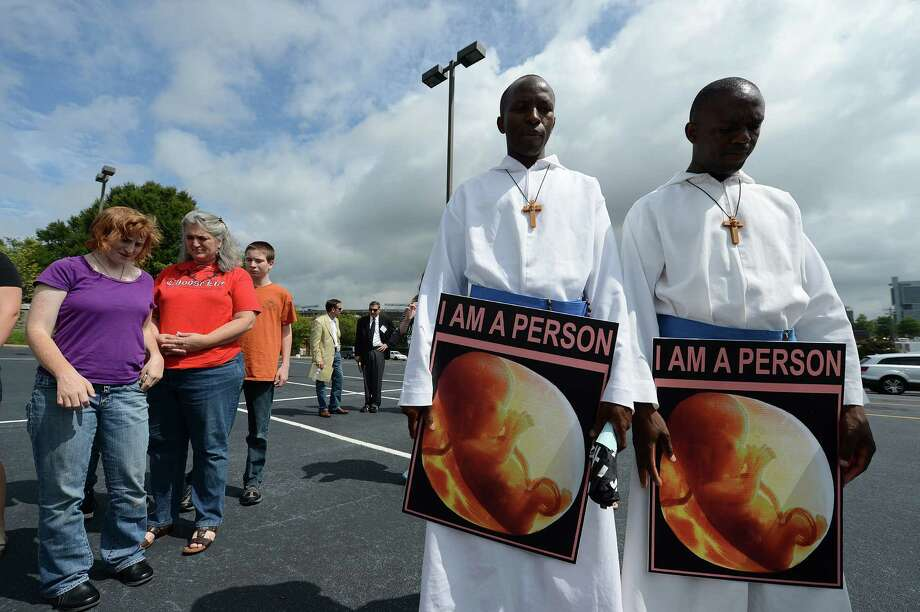 2012: Brother Peter (C) and Brother Pius (R) from Our Lady of Lourdes Catholic Church in Monroe, N.C., hold signs at an anti-abortion rights march and rally on day two of the  Democratic National Convention. (Photo credit should read ROBYN BECK/AFP/GettyImages) Photo: ROBYN BECK, Getty Images / 2012 AFP