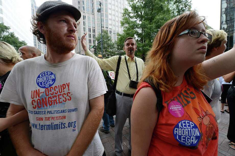 2012: Abortion rights activists encircle street preacher and anti-abortion activist Alex Burroughs on day two of the  Democratic National Convention (DNC), in Charlotte, N.C. (Photo credit should read ROBYN BECK/AFP/GettyImages) Photo: ROBYN BECK, Getty Images / 2012 AFP