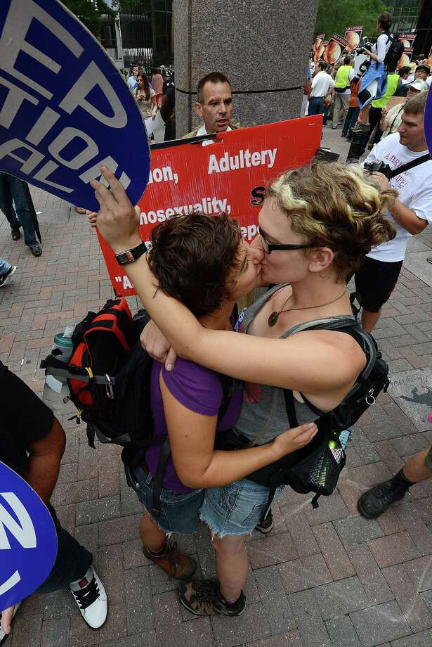 2012: Abortion rights protesters Annah Shapiro (L) and Kat Enyeart (R), both from Portland, Ore, kiss in front of street preacher Alan Hoyle on day two of the  Democratic National Convention (DNC), in Charlotte, N.C. (Photo by ROBYN BECK/AFP/GettyImages) Photo: ROBYN BECK, Getty Images / 2012 AFP
