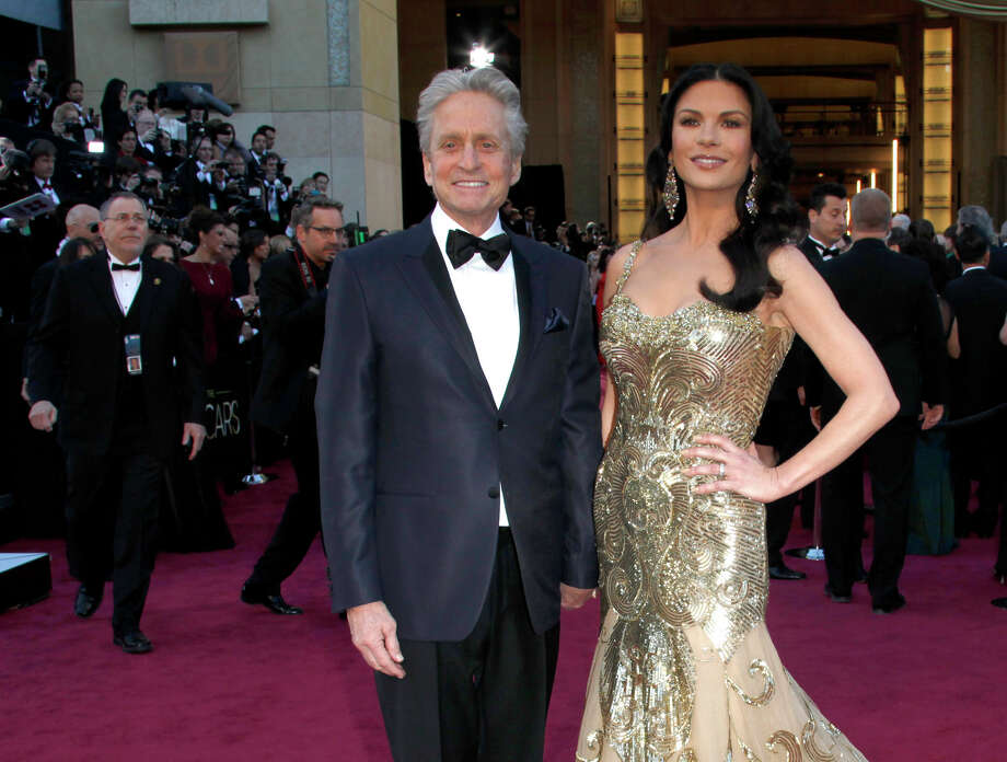 FILE - In this Feb. 24, 2013 file photo, actors Michael Douglas, left, and Catherine Zeta-Jones arrive at the Oscars at the Dolby Theatre, in Los Angeles. According to her publicist on Monday, April 29, 2013, Zeta-Jones has pro-actively checked into a health care facility. Previously, she has said that she is committed to periodic care in order to manage her health in an optimum manner. (Photo by Carlo Allegri/Invision/AP, File) Photo: Carlo Allegri