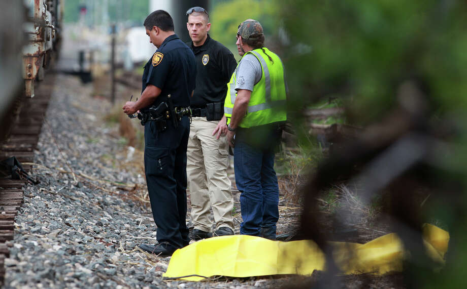 Police stand Tuesday morning April 30, 2013 near a body that was found by the railroad tracks near the 300 block of Cassiano. Police are still investigating the incident, but police said the man may have been hit by the train while collecting railroad spikes. Photo: JOHN DAVENPORT, SAN ANTONIO EXPRESS-NEWS / ©San Antonio Express-News/Photo may be sold to the public