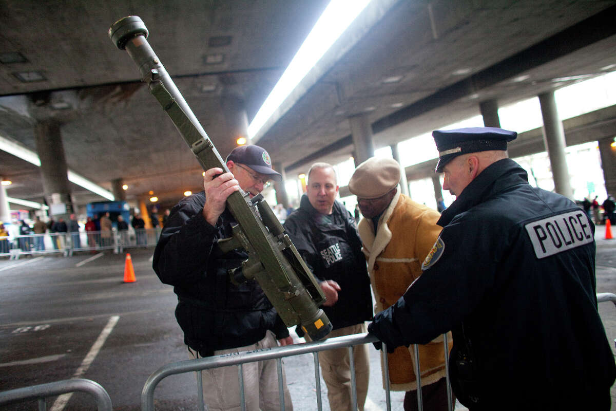 Seattle Police Department officers examine an inert surface to air missile launcher brought to the City of Seattle's gun buy back program on Saturday, January 26, 2013. The program handed out $80,000 worth of gift cards in exchange for weapons brought in by the public. The surface to air launcher was brought to the buyback and then purchased from a person in line for $100 by another citizen. Police took the already used, single use weapon until they could determine if it was safe and if the man could have it back.